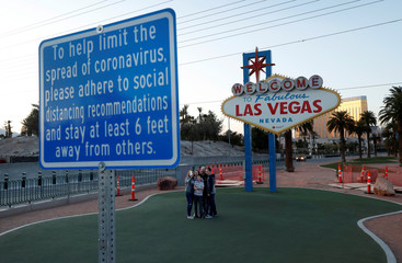 """A family takes a selfie at the normally crowded """"Welcome to Las Vegas"""" sign during the shutdown of all casinos and nonessential businesses to slow the spread of the novel coronavirus in Las Vegas"""