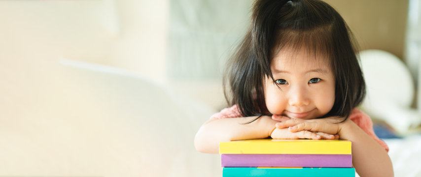 Panoramic portrait of Asian girl toddler smiling put her chin over her hands on the books stack. Education encourage concept.
