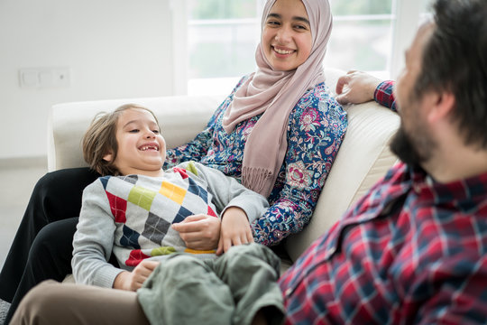 Middle Eastern family sitting on sofa in living roome at home