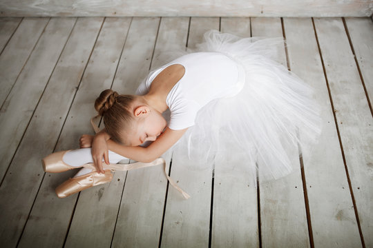 A little adorable young ballerina in white dress and point shoes lies like a swan on woody floor and gray studio background posing on camera