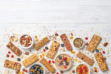 Energy healthy snack. Cereal granola bar with nuts and dry fruit berries. Fitness diet food. Protein muesli bars isolated on white wood. Sport oatmeal bar, top view