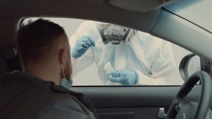 Patient is being tested in his vehicle on a drive-through coronavirus COVID-19 testing location. Pandemic, infection