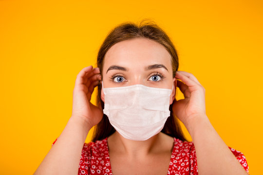 Portrait of a beautiful girl on a yellow background wearing a medical protective mask against coronavirus