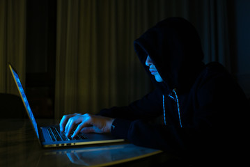 Hacker is  hacking into the computer network. Young boy in a dark room with laptop.  Hacker with a laptop.