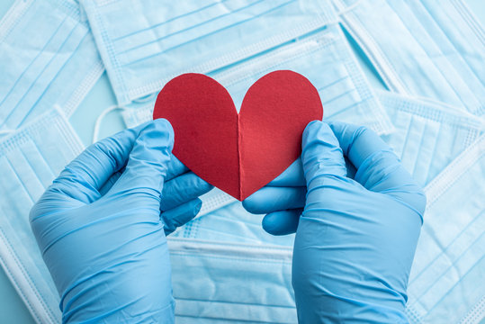 Medical staff holding red hearts in both hands