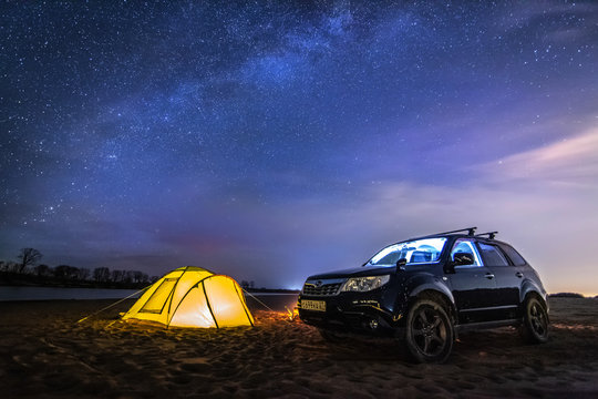Nikolaevka, Russia - May 04, 2019: Tourist tent and Subaru Forester under night starry sky