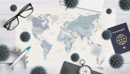 The concept of danger and inability to travel caused by the coronavirus epidemic. World map, passport, glasses, airplane, compass surrounded by corona viruses Wall mural