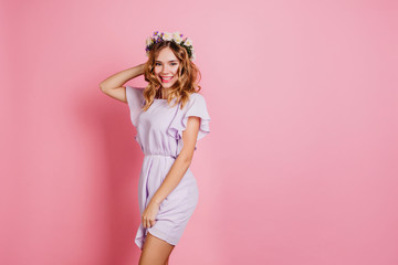 Wall Mural - Graceful white girl in wreath posing on pink background. Studio portrait of carefree caucasian lady with blonde wavy hair smiling to camera.
