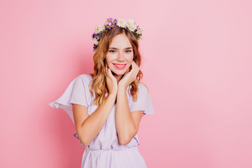 Wall Mural - Pleased girl with short wavy hair touching her face with smile. Indoor photo of attractive blonde lady in flower wreath.