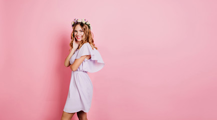 Wall Mural - Refined blonde woman in summer dress standing near pink wall with smile. Indoor portrait of positive girl in flower wreath enjoying photoshoot.