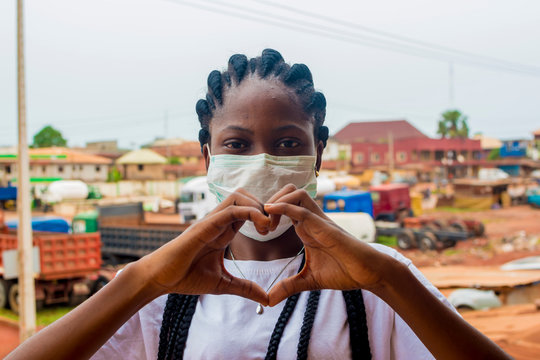 young black beautiful lady wearing a nose mask and giving a love sign with her hand