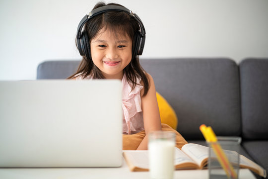 Asian girl using desktop computer for online study homeschooling during home quarantine. homeschooling, online study, home quarantine, online learning, corona virus or education technology concept