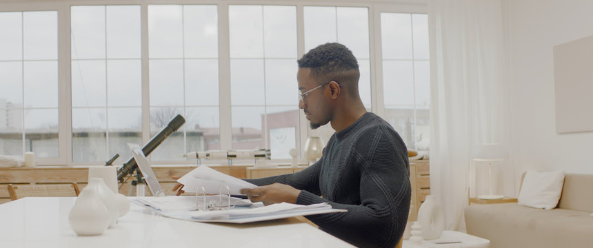 Handsome African American male working from home, using laptop in living room, checking documents