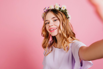 Wall Mural - Fashionable girl in flower wreath making selfie with gently smile. Close-up studio shot of enthusiastic white woman with wavy hairstyle.