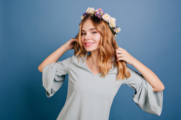 Wall Mural - Lovable white girl in flower wreath dancing on blue background. Studio portrait of short-haired caucasian woman in romantic dress posing with hands up.