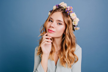 Wall Mural - Close-up portrait of white dreamy girl with shiny wavy hair. Studio shot of positive young lady in wreath isolated on blue background.
