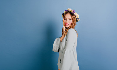 Wall Mural - Joyful white girl with beautiful flowers in hair posing on blue background. Indoor photo of lovable curly woman in vintage attire.