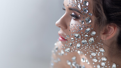 Fantastic fashion portrait of a young beautiful woman with transparent crystals on her face and shoulders. Fotomurales