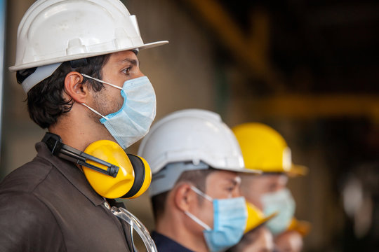 Workers wear protective face masks for safety in machine industrial factory.