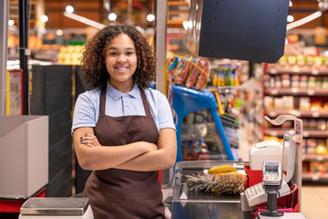 Pretty young smiling African-american female sales clerk looking at you