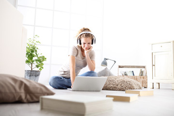 young woman sitting in living room studying with headphones and computer, stay at home concept Wall mural