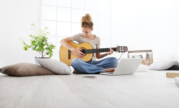 young woman sitting in living room playing guitar at the computer, stay at home concept