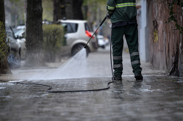 Public janitor deep cleaning the sidewalk with high pressure disinfectant solution in times of corona virus pandemic in a lockdown Bucharest, Romania