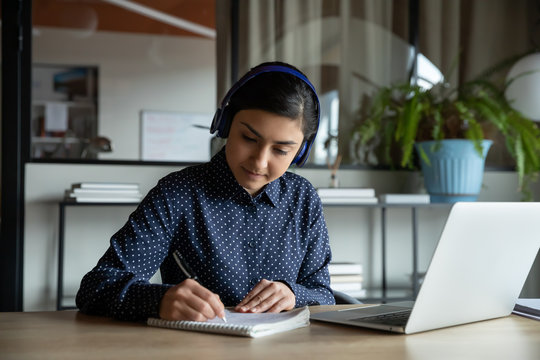 Focused young indian girl wearing wireless headphones, watching educational webinar lecture seminar, writing notes in paper copybook. Concentrated female student studying remotely on online courses.