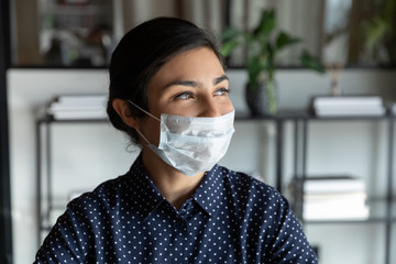 Happy young indian female company manager in protective mask looking away lost in thoughts, head...