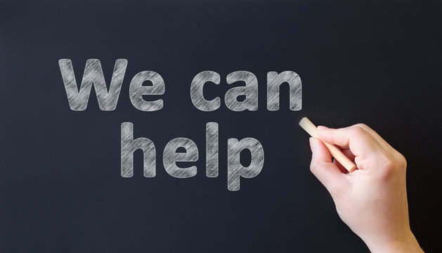 We can help - chalk inscription on a black chalk board. Hand with chalk writes text