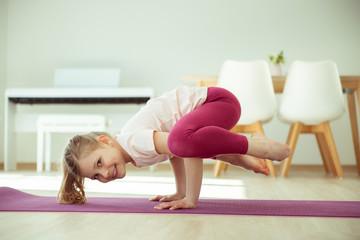 Pretty happy child girl making yoga exercises at home during coronavirus quarantine