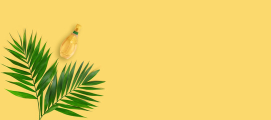 Minimal tropical green palm leaf with perfume in glass bottles  on yellow  paper background. Wall mural