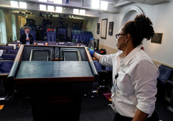 A custodian cleans the lectern in White House briefing room in Washignton