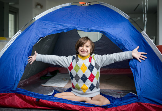 Kids having camping tent in living room for fun and adventure