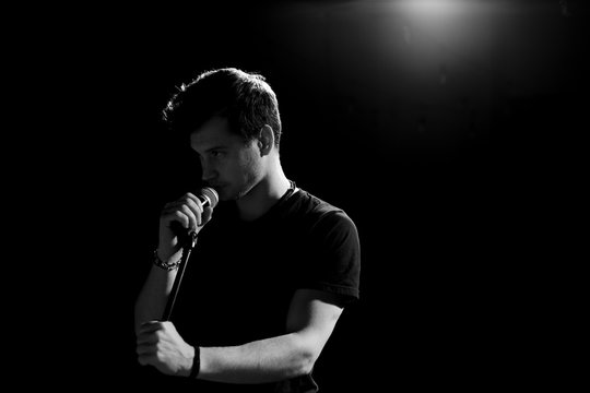 Young handsome guy emotionally sings and speaks into the microphone. Black and white photography