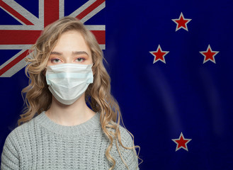 Young woman wearing a face mask with New Zealand flag. Flu epidemic and virus protection concept