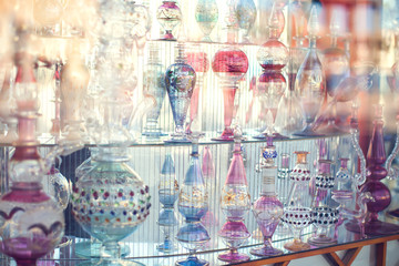 A lot of beautiful empty arabic style glass bottles for perfume in the shop behind the glass