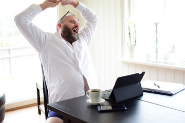 Deurstickers Ontspanning Freelancer man in a white shirt sits at a laptop and stretches, pulls his hands up. Concept: freelancer at home behind a laptop screen, remote work in quarantine.