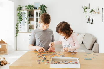 Brother and sister playing puzzles at home. Stay at home activity for kids.
