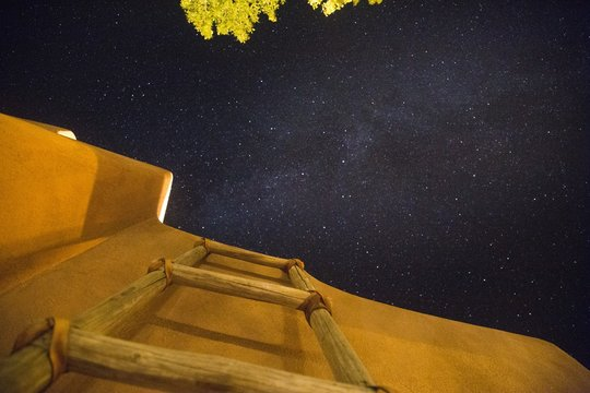 Low angle shot of a wooden ladder near the building under the dark sky full of stars