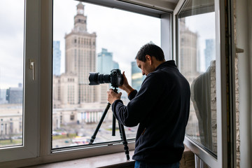 Young man in flat apartment with view of Warsaw, Poland cityscape taking picture with camera and tripod of famous Palace of Science and Culture building