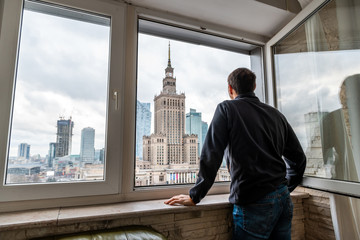 Young man standing looking in flat apartment with view of Warsaw, Poland famous Palace of Science and Culture cityscape building through window