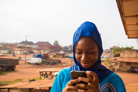 beautiful African muslim girl feeling excited as her is operating her cellphone.