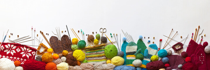 Knit for whole family. Panoramic view of knitting process and accessories: woolen yarns, needles and handmade warm things for children and adults on white background. Banner, copy space, flat lay Wall mural