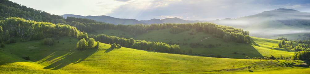 Panoramic mountain views, green hills and meadows. Morning light, fog. Fotobehang