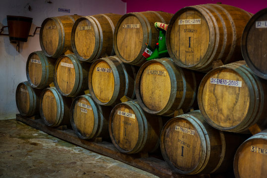 Stacked wooden barrels in Mexican tequila distillery.
