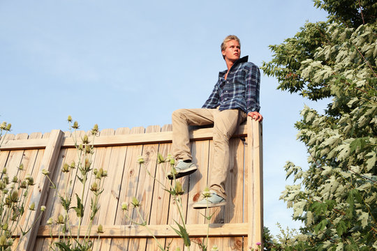 Serious teenage boy sitting on a fence, senior photo