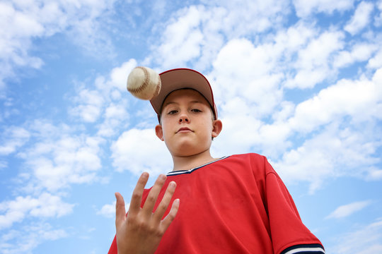 Boy pitcher tossing a baseball in the air, ready to pitch