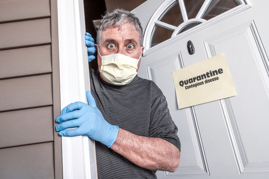 Man wearing mask and gloves afraid of virus exposure with quarantine sign