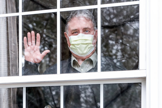 Man wearing mask with his hand up waving at the window